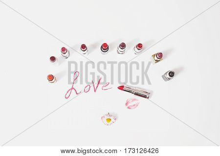 Lipstick lie on white background. Female lip pencil makeup. Kiss of lips on paper. The word love written in lipstick. Reflection of lipstick in the mirror. View from above. Makeup concept. Decorative cosmetics makeup