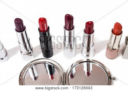 Lipstick isolated on white background. Female lip pencil makeup. Kiss of lips on paper. The word love written in lipstick. Reflection of lipstick in the mirror. View from above. Makeup concept. Decorative cosmetics makeup