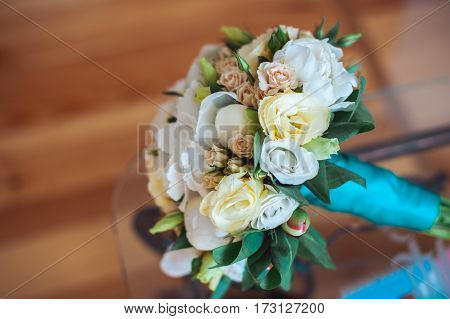 wedding Bouquet of white roses with a blue ribbon on the glass table in a room
