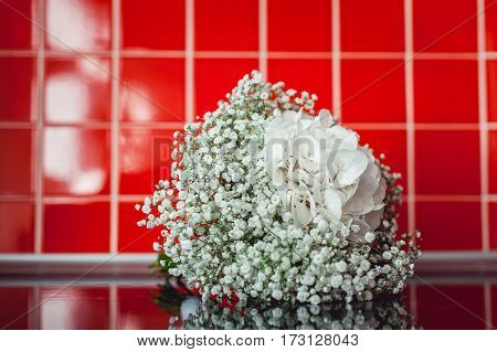 wedding bouquet of white gypsophila and hydrangea white ribbon on a black table in a front of red tile