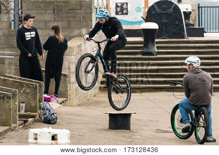 Cardiff Wales UK - February 18 2017: Bike riders performing tricks on street furniture. Young men make jumps for fun with friends standing around