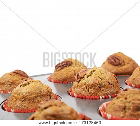 Muffin pan tray full of freshly baked pekan nut cupcakes isolated over the white background, close-up crop fragment