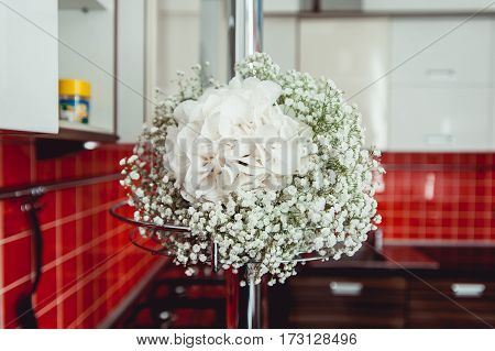 wedding bouquet of white gypsophila and hydrangea white ribbon on a chrome bar in a front of red tile