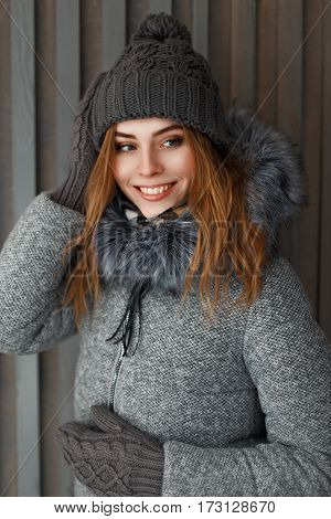 Beautiful Happy Girl With A Smile In A Winter Jacket And A Gray Knit Hat Near The Wooden Wall