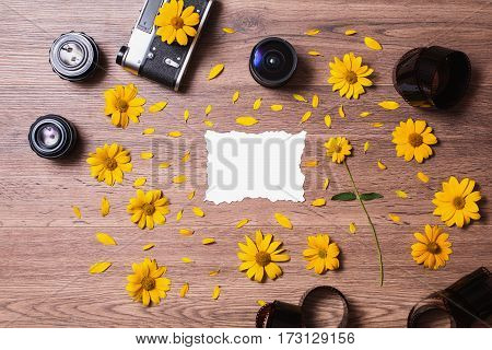 Old vintage camera on wooden background with yellow petals and flowers. Manual focus lenses and film are on the table with a white sheet of bumagi.Plosky lie. Layout