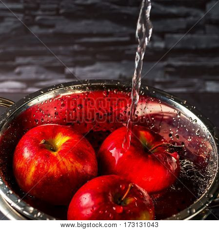 Three red apples in a metal bowl. Apples under running water. Wash apples. Healthy food concept