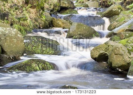 Close up on the fast flowing water of Burbage Brook in the rocky river valley of Padley Gorge, Longshaw Estate, Peak District, UK