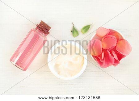 Skincare herbal cosmetics daily set, top view. Jar of cream, pink rose petals, facial tonic in bottle.