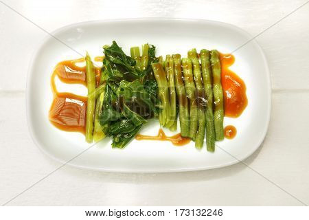 Vegetable fast food idea menu kale and yard long bean boiled with sauce oyster in white dish.