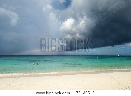 Grand Turk island beach with dark rainy cloud and a rainbow (Turks & Caicos).