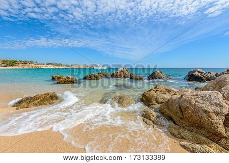 Fantastic sky, ocean and rocks. Differen stages of the waves on the ocean sand. Playa El Chileno Beach, Cabo San Lucas, Mexico.