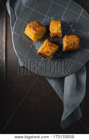 Slices of roasted corn on ceramic plate vertical