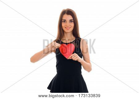 young beautiful brunette woman in stylish black dress with red heart in her hands looking at the camera and smiling isolated on white