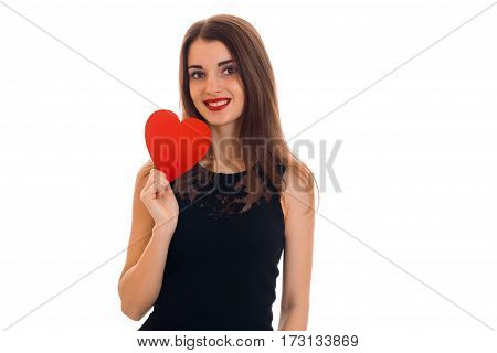young attractive brunette woman in stylish black dress with red heart in her hands looking at the camera and smiling isolated on white