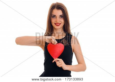 young beauty brunette woman in stylish black dress with red heart in her hands looking at the camera and smiling isolated on white