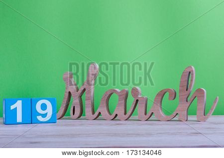 March 19th. Image of march 19 wooden color calendar with flower on white background. Spring day. Earth Hour and International client's Day.