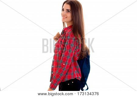 stylish cheerful brunette student girl with blue backpack looking away and smiling isolated on white
