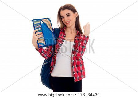 stylish cheerful brunette student girl with blue backpack and folder for notebooks in her hands looking at the camera and smiling isolated on white
