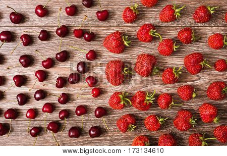 The texture of berries. Ripe juicy red cherry and a big red strawberry lying on a wooden background. Sweet summer berries. Flat lay. top view. Fresh berries. Berries on the table. .