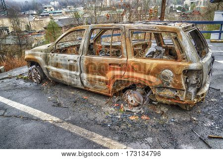 GATLINBURG TENNESSEE/USA - DECEMBER 14 2016: A burned-out car waits for clean-up crews in the aftermath of a massive forest fire that destroyed part of Gatlinburg TN in late 2016.
