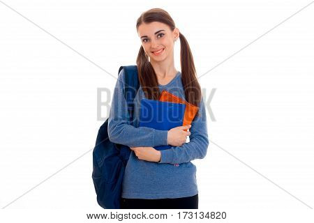 stylish happy brunette student girl with blue backpack and folder for notebooks in her hands looking at the camera and smiling isolated on white