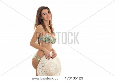 young lovely brown hair lady with big natural breasts in swimsuit with floral pattern looking and smiling on camera and hide her panties behind a straw hat isolated on white.