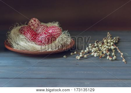 Still life with Pysanka decorated Easter eggs dry willow branches on black wooden background copy space