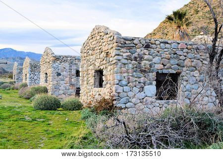 Row of abandoned stone cottages taken on a rural field at Mission Creek Preserve in the California Desert