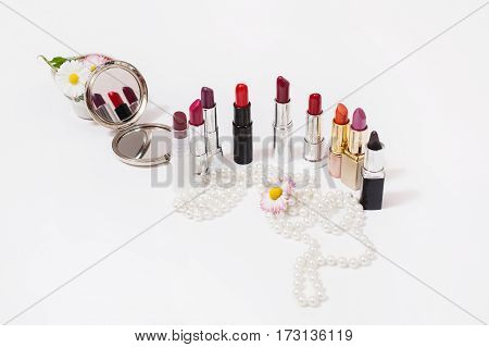 Multicolored glossy lipstick on white background. Wild purple flower on a white surface. Female white beads. Cosmetic products for painting lips. View from above. Makeup accessories