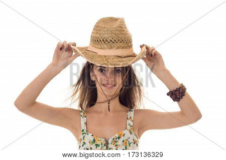 young lovely girl in sarafan with floral pattern and straw hat looking and smiling on camera isolated on white