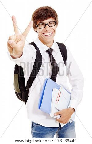 Young hispanic man with backpack wearing glasses, blue jeans, white shirt and black tie, holding books and folder in his hand, smiling and showing victory hand gesture isolated on white background