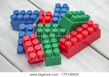 Plastic toy blocks on a wooden backgroundon a wooden background