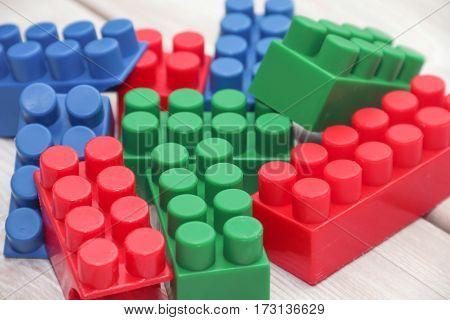 Plastic toy blocks on a wooden backgroundon