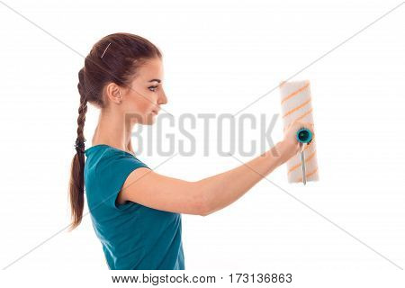 studio profile portrait of young beautiful brunette girl in uniform makes renavation with paint roller in hands isolated on white