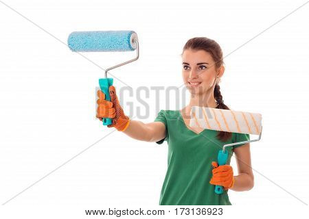 studio portrait of young happy brunette girl in uniform makes renavation with paint roller in hands smiling isolated on white