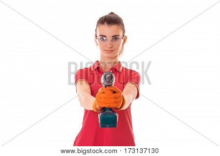 studio portrait of young beautiful brunette girl in uniform and glasses makes renavation with drill in hands isolated on white