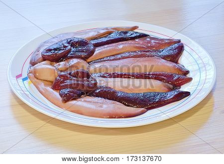raw eggs and milt in the bag of herring lie horizontally in a ceramic white dish on wooden table