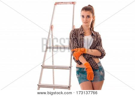 studio portrait of young lovely girl in uniform makes renavation on ladder looking at the camera isolated on white