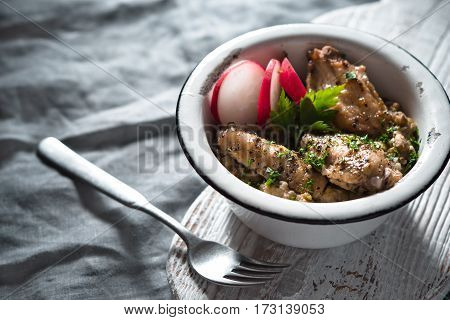 Pilaf with chicken in a metal bowl and radishes side view horizontal