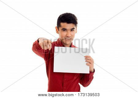 stylish young brunette male model in red t-shirt posing with empty placard in his hands smiling on camera isolated on white