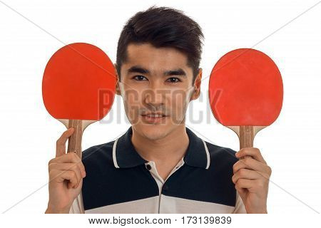 portrait of handsome sportsman with rackets in his hands and uniform practicing table tennis on camera isolated on white