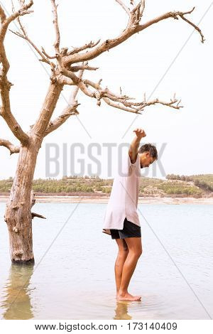 young male balancing on a rock in a flooded lake with a dead tree in the water. concept of climate change filter added blank sky in background for copy space