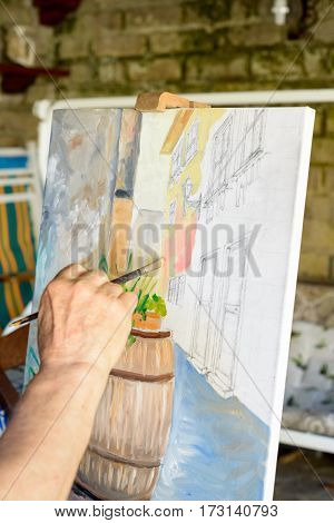 Hand of a Senior Man painting a picture with oil colors