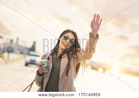View at young woman hailing a taxi on the street in the city