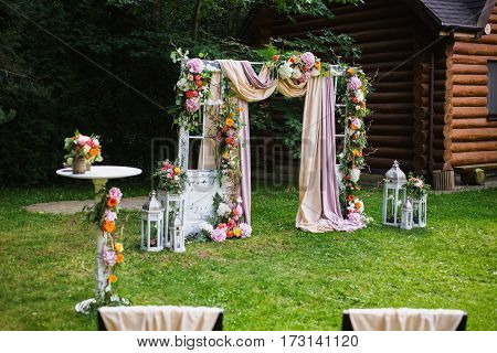 Beautiful wedding ceremony outdoors. Decorated chairs stand on the grass. Wedding arch made of cloth and white and pink flowers on a green natural background. Old doors rustic style.