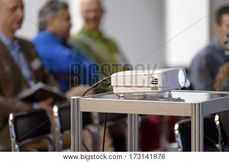 White multimedia projector in a conference room with blured people on the background