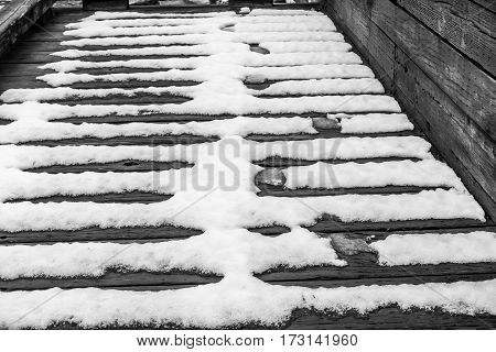 Snow melts on a wooden walkway creating an interesting pattern.