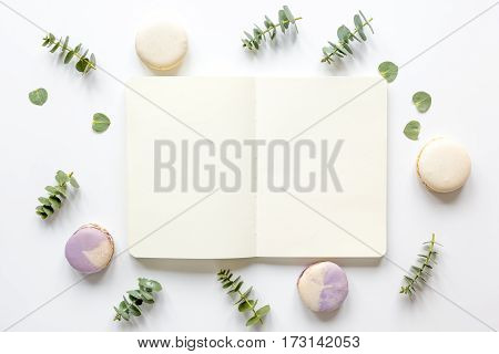 Trendy spring design in pastel color with macaroons and flowers on white background top view mockup