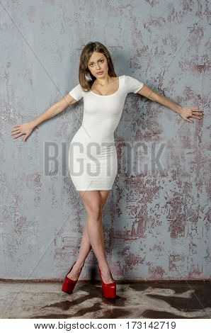 Young go go girl with a beautiful figure in a trendy white dress in skin-tight jacket and red high heels and platform  dressed for a party
