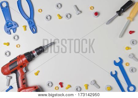 Toys tools as border frame on white background. Top view. Copy space for text